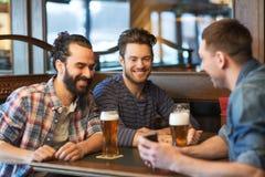 Amis masculins avec de la bière potable de smartphone à la barre Photos stock