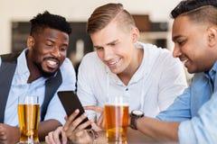 Amis masculins avec de la bière potable de smartphone à la barre Photo libre de droits