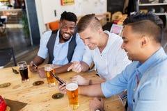 Amis masculins avec de la bière potable de smartphone à la barre Image stock