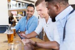 Amis masculins avec de la bière potable de PC de comprimé à la barre Images stock
