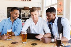Amis masculins avec de la bière potable de PC de comprimé à la barre Photo stock