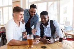 Amis masculins avec de la bière potable de smartphone à la barre Image libre de droits