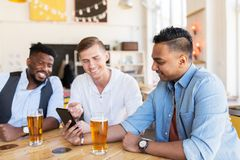 Amis masculins avec de la bière potable de smartphone à la barre Photos libres de droits