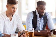 Amis masculins avec de la bière potable de smartphone à la barre Images stock