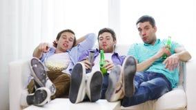 Amis masculins avec de la bière regardant la TV à la maison banque de vidéos
