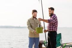 Amis masculins avec des poissons et des cannes à pêche sur le pilier image stock