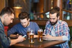 Amis masculins avec des smartphones buvant de la bière à la barre Image libre de droits
