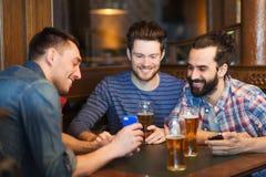 Amis masculins avec des smartphones buvant de la bière à la barre Photo stock