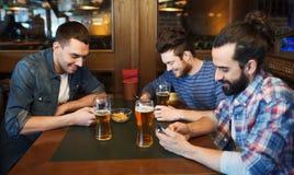 Amis masculins avec des smartphones buvant de la bière à la barre Image stock