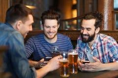 Amis masculins avec des smartphones buvant de la bière à la barre Photos stock