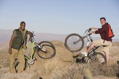 Amis masculins avec des vélos de montagne sur des roches Images libres de droits
