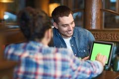 Amis masculins avec le PC de comprimé à la barre Images stock