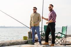 Amis masculins avec les cannes à pêche et la bière sur le pilier images stock