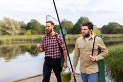 Amis masculins avec les cannes à pêche nettes et sur le lac images libres de droits