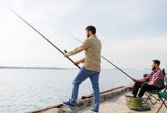 Amis masculins avec les cannes à pêche sur la jetée de mer photographie stock