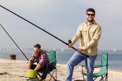 Amis masculins avec les cannes à pêche sur la jetée de mer image stock