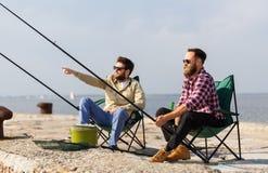 Amis masculins avec les cannes à pêche sur le pilier photographie stock libre de droits