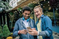 Amis masculins avec plaisir discutant un nouveau smartphone images libres de droits
