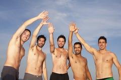 Amis masculins ayant l'amusement sur la plage Photo stock