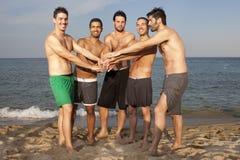 Amis masculins ayant l'amusement sur la plage Photo libre de droits