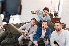 Amis masculins beaux regardant dans l'appareil-photo de smartphone Photos stock