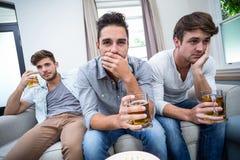 Amis masculins bouleversés buvant l'alcool tout en regardant la TV Photo libre de droits