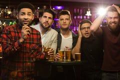 Amis masculins bouleversés observant le jeu de sport ou le match de football Photos libres de droits