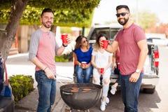 Amis masculins buvant de la bière dans un barbecue Photo stock