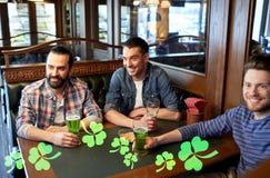 Amis masculins buvant de la bière verte à la barre ou au bar Images stock
