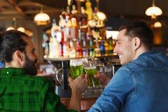 Amis masculins buvant de la bière verte à la barre ou au bar Photos stock
