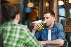Amis masculins buvant de la bière verte à la barre ou au bar Image libre de droits