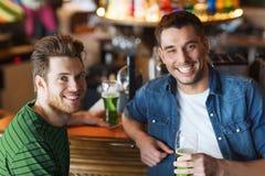 Amis masculins buvant de la bière verte à la barre ou au bar Photo stock