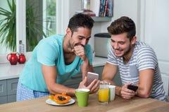 Amis masculins de sourire à l'aide du téléphone Images libres de droits