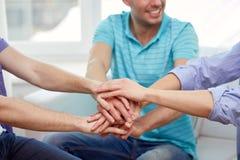 Amis masculins de sourire avec des mains ensemble à la maison Photos libres de droits