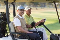 Amis masculins de sourire de golfeur s'asseyant dans le boguet de golf Photos stock