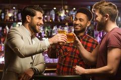 Amis masculins de sourire heureux faisant tinter avec des tasses de bière Image libre de droits