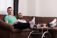 Amis masculins de sourire jouant des jeux vidéo à la maison Images stock