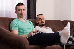 Amis masculins de sourire jouant des jeux vidéo à la maison Images libres de droits