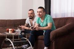 Amis masculins de sourire jouant des jeux vidéo à la maison Photographie stock libre de droits