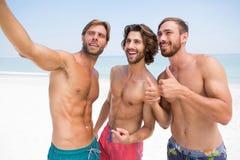 Amis masculins de sourire se tenant à la plage Images libres de droits