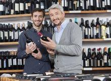 Amis masculins de sourire tenant des bouteilles de vin Photos libres de droits