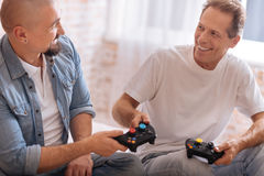 Amis masculins de sourire tenant des consoles de jeu à la maison Images libres de droits
