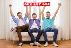 Amis masculins de sourire tenant le signe de vente Photo libre de droits