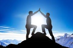 Amis masculins donnant la haute cinq sur la crête de montagne Images stock