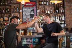 Amis masculins donnant la haute cinq tout en se reposant dans la barre Photo libre de droits