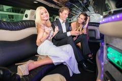Amis masculins et féminins élégants heureux avec la bouteille de champagne et Images stock