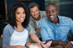 Amis masculins et féminins avec le téléphone portable dans le café Images libres de droits