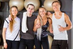 Amis masculins et féminins de séance d'entraînement se tenant ensemble dans le gymnase Photo stock