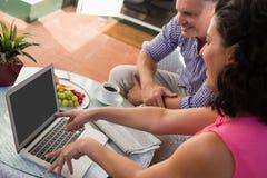 Amis masculins et féminins discutant au-dessus de l'ordinateur portable en café extérieur Image stock