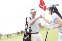 Amis masculins et féminins donnant le top-là au terrain de golf Images libres de droits